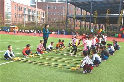 街道中心幼儿园的孩子们沉浸在欢快的跳竹竿游戏中